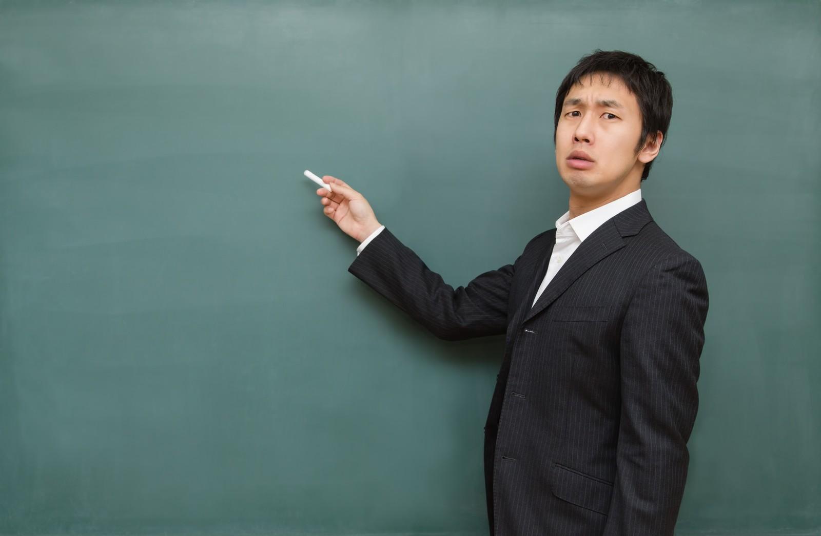 黒板の前に立つ男性