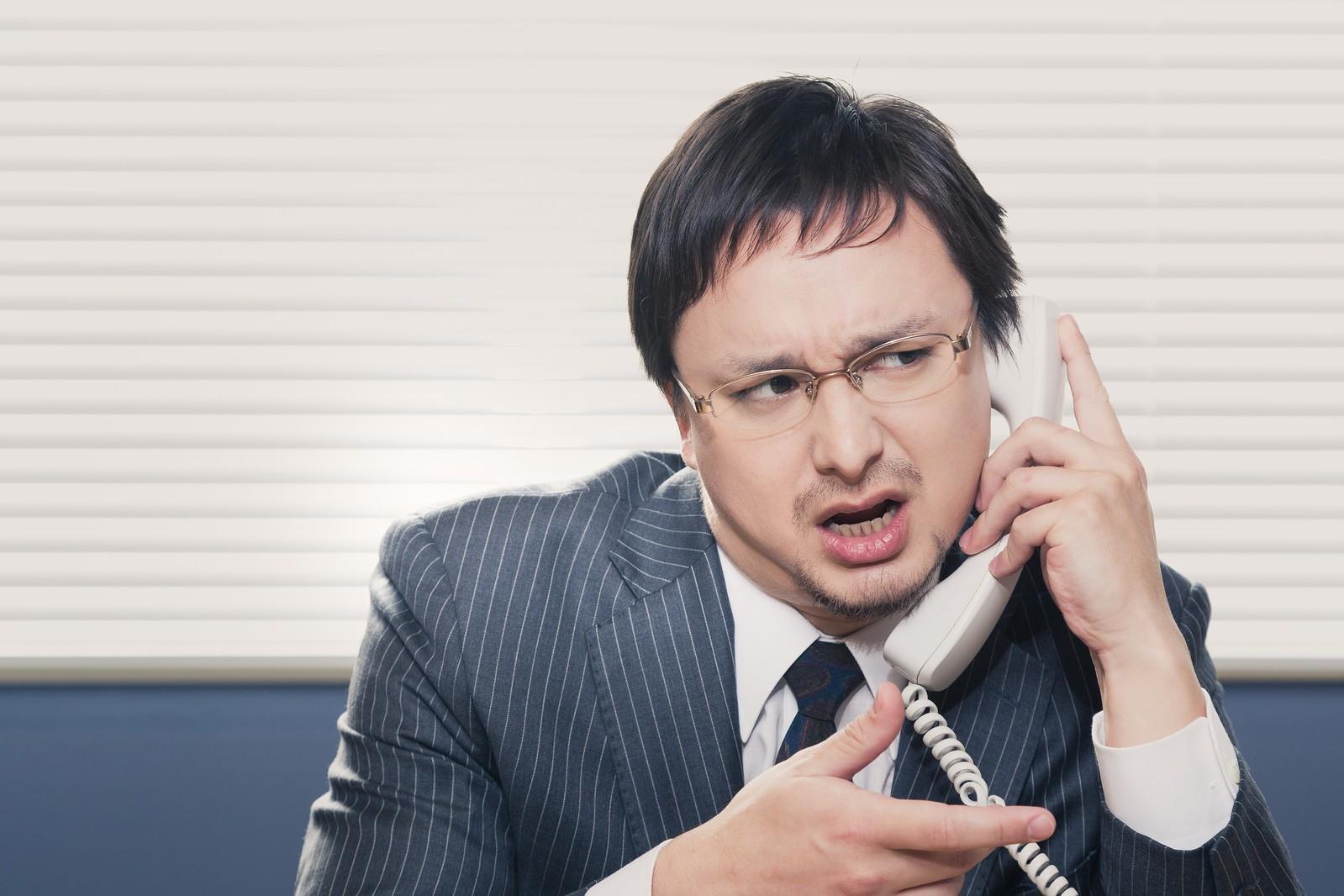 電話で話す男