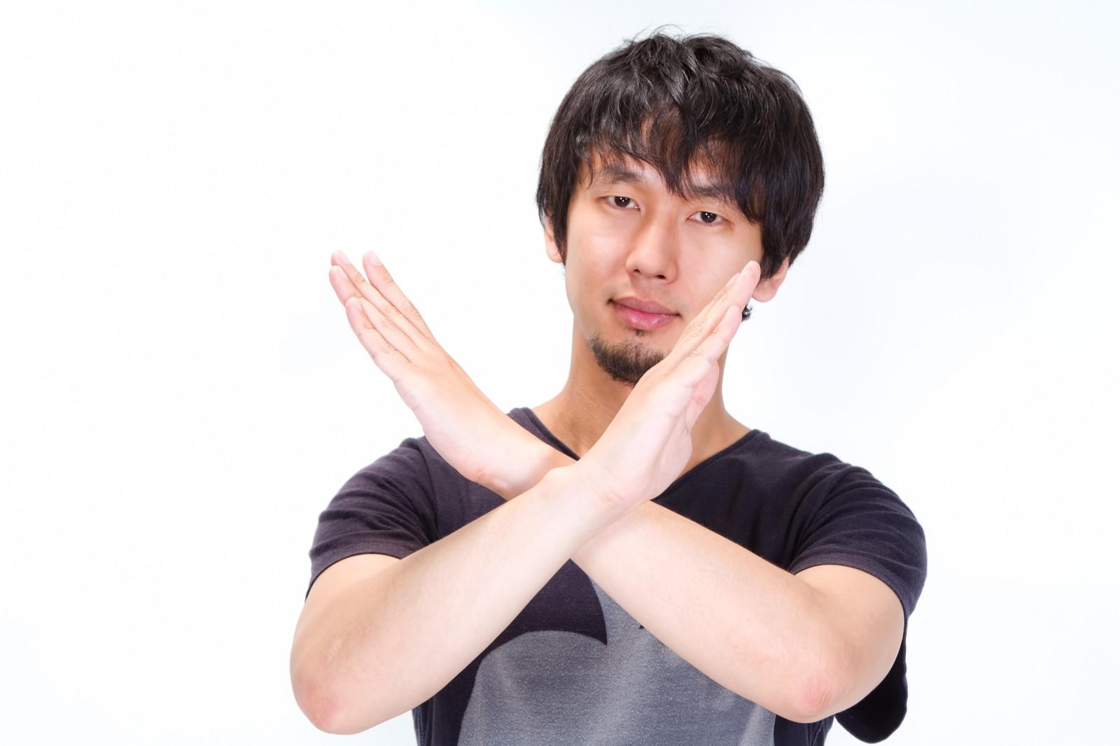 手で✕印を示す人